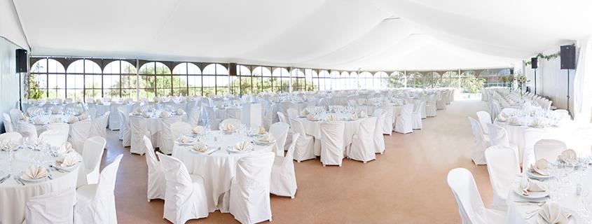 Eventfirmen-Projekt: Festzelt von innen mit weiß gedeckten Tischen