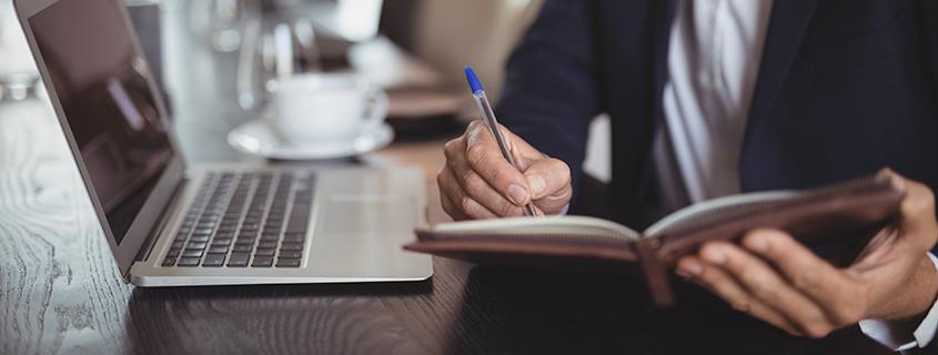 Geschäftsmann schreibt für sein Unternehmen in sein Notizbuch mit offenem Laptop auf Cafétisch